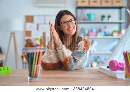 Young beautiful teacher woman wearing sweater and glasses sitting on desk at kindergarten clapping and applauding happy and joyful, smiling proud hands together
