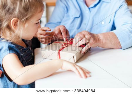 Grandmother And Child Prepare Gifts For Family. Kid And Senior Woman Wrap Gift With Ribbon And Bow.