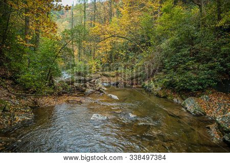 A Fast Current River Flowing Downstream Rapidly Along The Rocks And Boulders With Colorful Autumn Tr