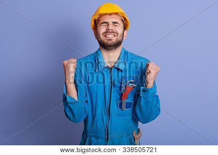 Horizontal Picture Of Exhausted Construction Worker Clenching His Fists, Raising Hands, Closing Eyes