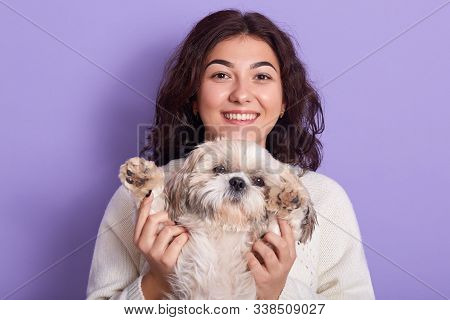 Horizontal Shot Of Positive Funny Model With Peaceful Facial Expression, Raising Maltese Paws, Spend