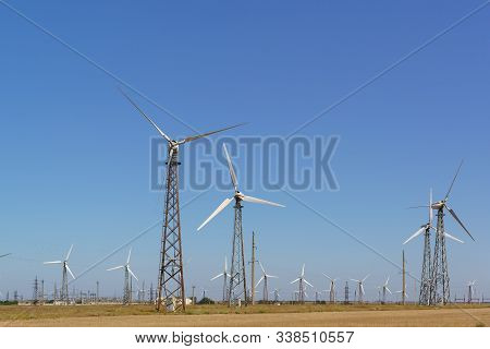 Huge Blades Of A Wind Generator On A High Mast In The Crimean Steppe . An Inexhaustible Source Of En