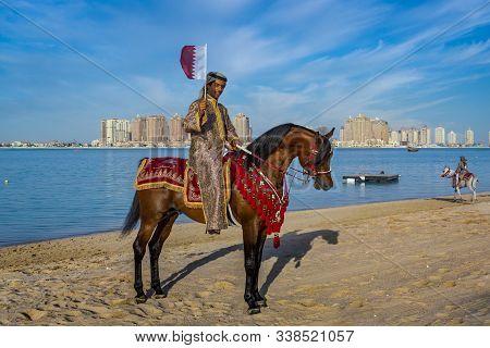 Doha,qatar-december 18,2013: A Qatari Man Riding A Horse And Carry Qatar Flag In Katara Beach Celebr