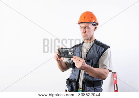 The Builder Is Filming On The Camera A Mobile Phone. In A Helmet And Work Clothes. For Any Purpose.