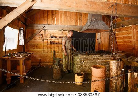 Gudvangen, Norway - June 13 - The Young Man In Blacksmith Clothes In The Viking Village Museum.