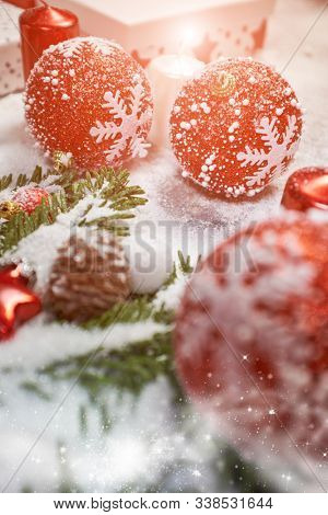 Christmas background or xmas greeting card. Red christmas present box, fir tree branch and decorations on gray stone table. Top view with copy space.