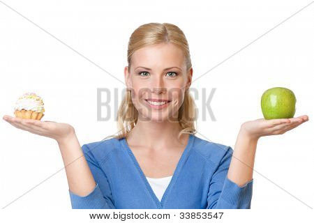 Attractive woman makes a tough choice between cake and apple, isolated on white
