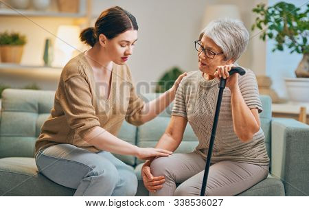 Elderly patient and caregiver spending time together. Senior woman holding cane.