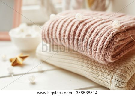 Christmas Background From Knitted Things. Winter Concept. A Stack Of Cozy Knitted Sweaters, Scarves.
