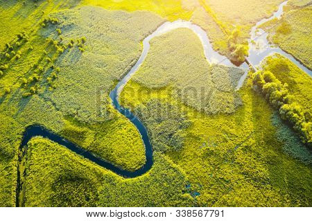 Aerial drone view of winding river in green field. Lush wetlands of bird's eye view. Location place countryside of Ukraine, Europe. Textural image of drone photography. Discover the beauty of earth.