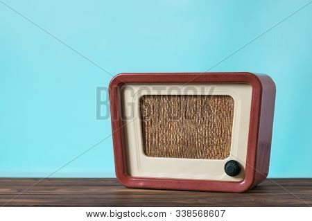 Vintage Radio On A Wooden Table On A Blue Background. Radio Engineering Of The Past Time. Retro Desi