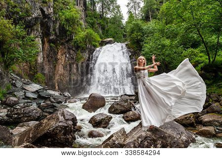 A Young Blonde Girl In An Elegant Pose Pulls Up A Boudoir Dress In The Mountains Against A Waterfall