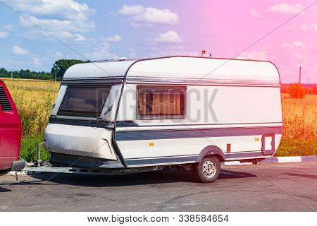 A Motor Home In The Form Of A White Trailer In A Parking Lot Near The Road, Secured To The Car While