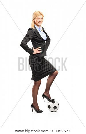 Full length portrait of a woman in high heels standing on a soccer ball isolated on white background