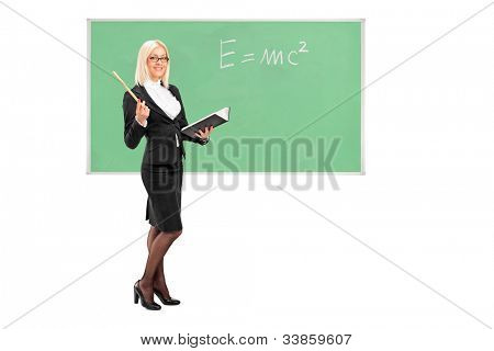 Full length portrait of a female teacher with a book in her hand and chalkboard in the background