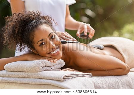 Young woman receiving hot stone massage at health spa and looking at camera. Portrait of relaxed african woman getting lastone therapy at spa resort. Masseuse getting lava stones on girl back.
