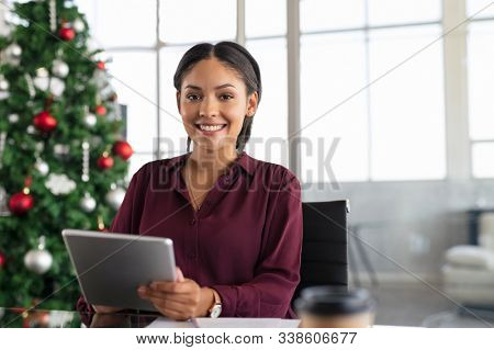 Happy business woman using digital tablet in modern office with christmas tree in background. Portrait of young middle eastern woman smiling and looking at camera during christmas time with copy space