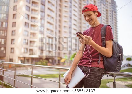 Smiling teenager  looks to the cell phone screen, in the city.  Young man stands with a smartphone, in the street.  Happy teenage boy is using mobile phone, outdoors. Soft focus effect.