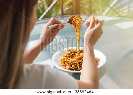 Close Up Of Woman Eating Spaghetti With Fork And Tablespoon