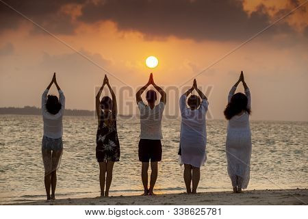 Silhouettes Of Five People Staying At The Beach On Beautiful Sunset. Sup Yoga Meditation, Harmony Wi