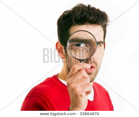 Curious young man looking through magnifying glass, isolated on white