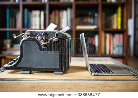 Old Vintage Dust-covered Typewriter With Sheet Of White Paper Near Modern Notebook On Bookcase Backg