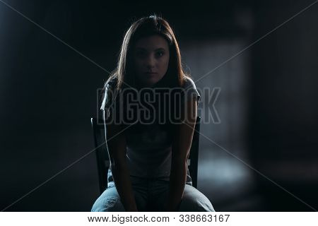 Hopeless Young Woman Looking At Camera While Sitting On Chair In Darkness On Black Background