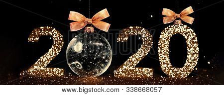 Christmas toy. The numbers 2020 are written from sparkles. Template for a festive New Year card from beautiful bokeh. Happy New Year 2020. New Year's decoration. Holiday concept.