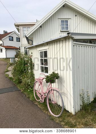 July 29, 2019 - Skärhamn, Sweden. Summer Homes In Sweden. A Bicycle Rests Against A Traditional Hous