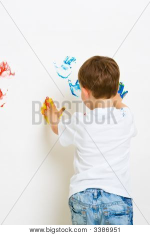 Child Making Hand Prints On The Wall