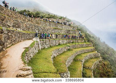 Machu Picchu, Peru-Jan 16, 2019: Tourists on former agricultural terraces at Machu Picchu ruins, Peru. South America.