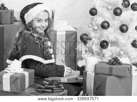 Wish List. Girl Little Kid Hold Pen And Paper Near Christmas Tree Writing Letter. I Was Good Girl Al