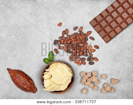 Bar Of Milk Chocolate, Cocoa Butter, Cocoa Pod, Cocoa Beans, Cane Sugar Cubes And Mint On Gray Stone