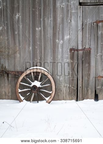 Old Wooden Barn Wall With An Old Wooden Cartwheel Standing In Front Of It. With Snow On Cartwheel An