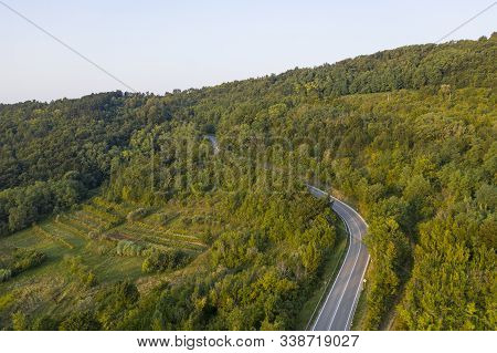 A Narrow Winding Road Runs Along The Populated Slope Of The Mountain. There Is A Vineyard On The Mou