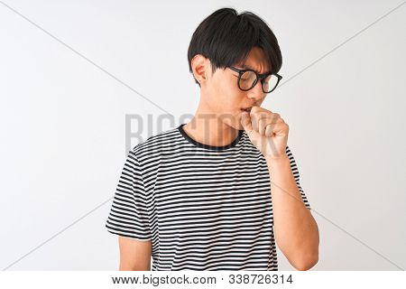 Chinese man wearing glasses and navy striped t-shirt standing over isolated white background feeling unwell and coughing as symptom for cold or bronchitis. Healthcare concept.