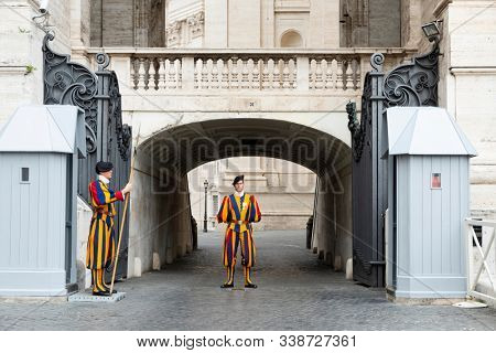VATICAN CITY, VATICAN - OCTOBER 15, 2019: Members of the Pontifical Swiss Guard, one of them with halberd at his sentry box, guarding the entrance to the private compound of the Holy See