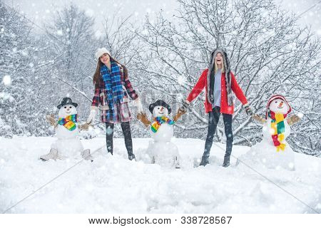 Group Of Beauty Winter Girls With Snowman. Students Party And Christmas Celebration. Two Joyful Beau