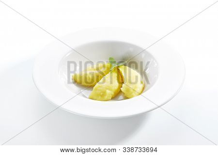 Exquisite serving mashed potato or mash on white restaurant plate isolated. Delicious creamy puree made of potatoes with butter and spinach side view