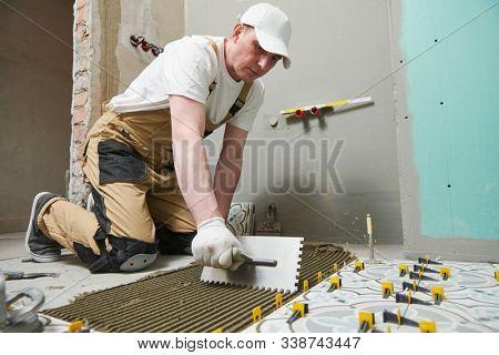 Tiler installing tile on bathroom floor. home indoors renovation