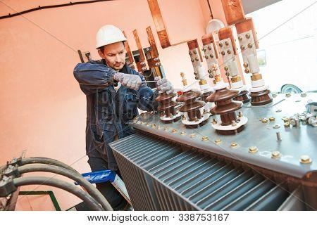 Electrician lineman worker installing power industrial transformer