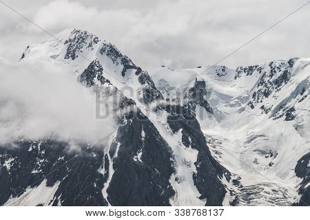 Atmospheric Minimalist Alpine Landscape Of Big Snowy Mountain With Massive Glacier. Low Cloud Among