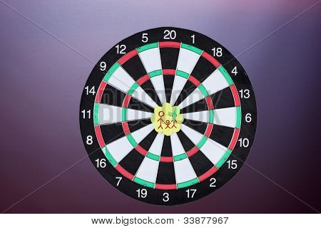 Darts with stickers depicting the life values on colorful background. The darts hit the target