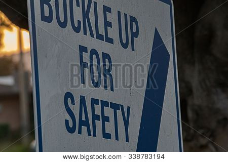 Buckle Up For Safety Sign In Blue And White Block Letters