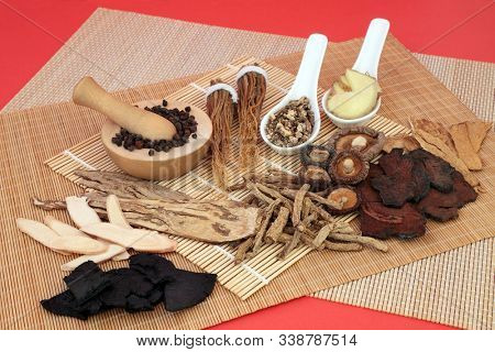 Chinese herbs used as a tonic in traditional herbal medicine on bamboo & red background. Oriental health care concept.