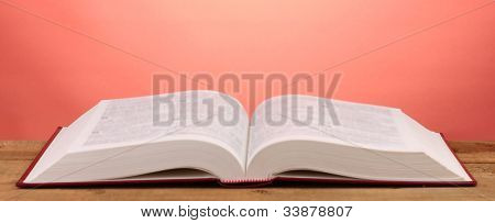 Open book on wooden table on red background
