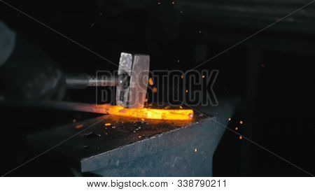 Forge Workshop. Smithy Manual Production. Hands Of Smith With Hammer Hit On Glowing Hot Metal, On Th