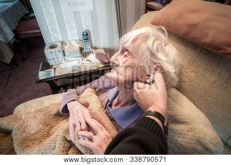 Elderly Woman Is Given Anti Bacterial Ear Spray By Her Carer At Her Home.