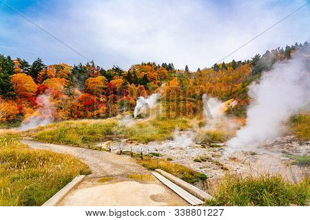 View Of Fuke No Yu Hot Spring In Autumn Season With Colorful Foliage On The Mountain And White Steam