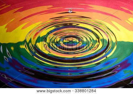 A single water droplet falling towards the centre of a water splash reflecting the Rainbow Pride Extinction Rebellion flag and logo. Abstract Extinction Rebellion climate change background.